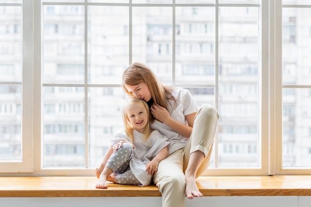 窓の前に座って小さな娘にキスを与える若い母親。幸せなママが一緒に楽しんでいる間かわいい女の子を抱擁します。