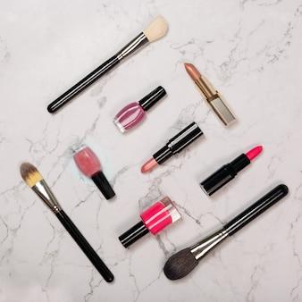 口紅、マニキュア、白い大理石の背景に化粧ブラシを含む化粧品のフラットレイアウト