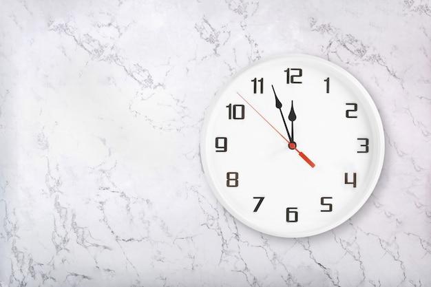 白い天然大理石の背景に白い丸い壁時計。