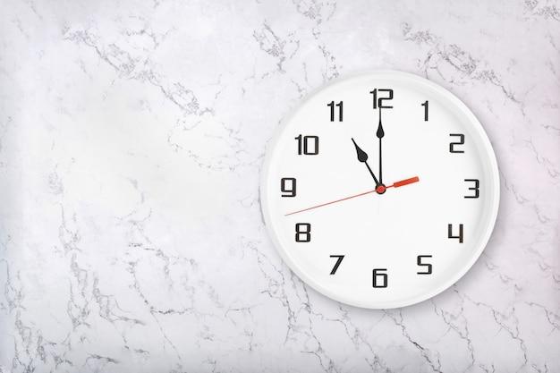 Белые круглые настенные часы на белой естественной мраморной предпосылке. одиннадцать часов