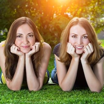 草の上に横たわる幸せな笑顔の若い女性
