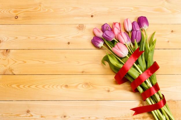 Букет тюльпанов с красной лентой на деревянной текстуры. день святого валентина фон