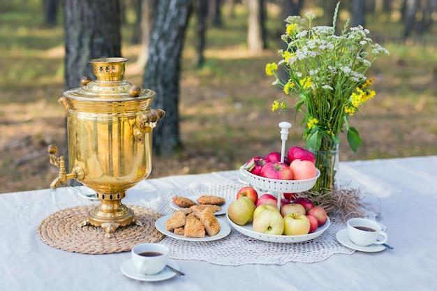 Традиционный самовар на столе с закусками и букетом полевых цветов на открытом воздухе