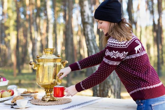 ヴィンテージのロシアのティーポットサモワールを使用していくつかのお茶を注ぐ帽子とジャージを着た若い女性