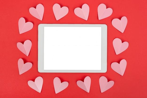 タッチパッドと紙の心とバレンタインデーの背景。平置き。