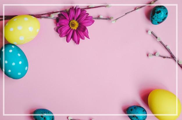イースターウズラの卵、春の花、ピンクの背景に柳