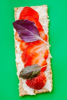 クリスプブレッド、クリームチーズ、イチゴ、バジルの緑の背景に軽食