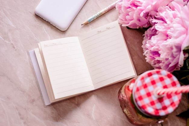 Салон плоской планировки с дневником, смартфоном, аксессуарами и пионами на мраморном фоне