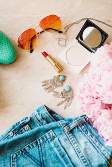 ファッションフラットを置きます。ジーンズ、靴、アクセサリーとピンクの牡丹の花