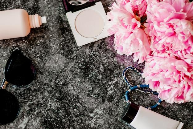 ビューティーフラット、アクセサリー、香水、化粧品、暗い大理石の背景に牡丹を置く