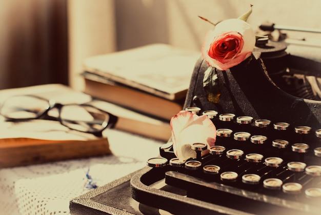 ピンクのバラとヴィンテージのタイプライター、テーブルの上の古い本。