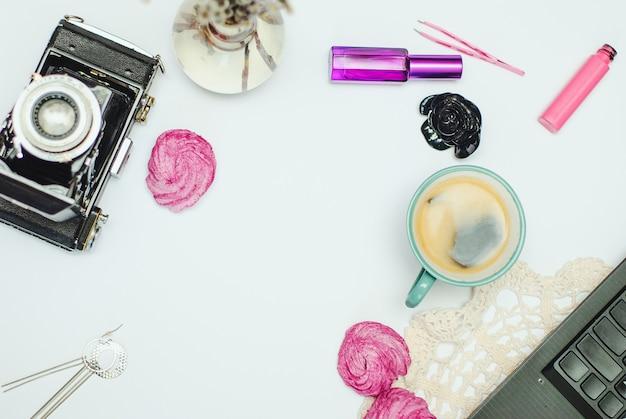 Плоский стол с кофе, зефиром, ноутбуком, винтажной камерой и косметикой