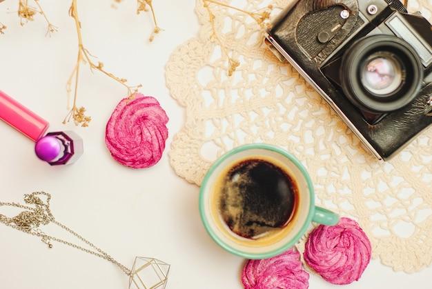 Плоский стол с кофе, зефиром, винтажной камерой и косметикой