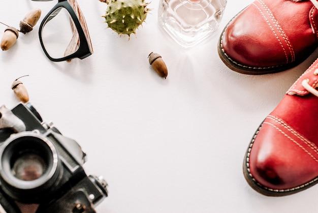 Красные сапоги лежат с камерой, очками и желудями.