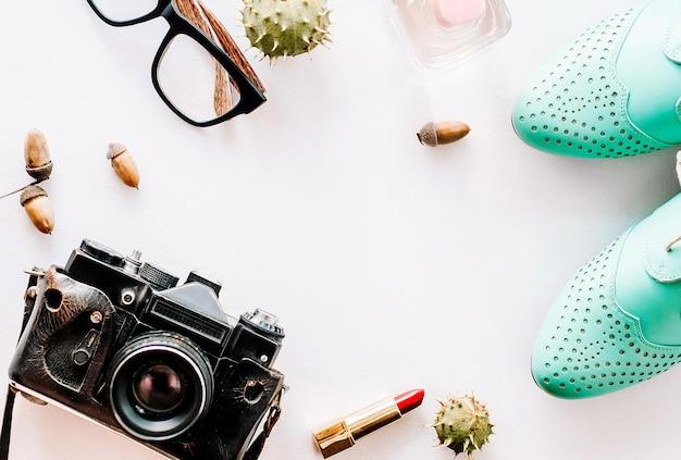 Модные кожаные туфли лежат с камерой, очками и желудями.