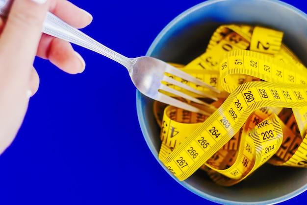 ダイエットの概念皿のクローズアップの上に横たわるフォーク巻き戻しセンチ