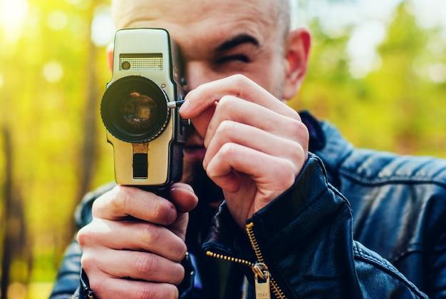 古いフィルムカメラを持つ若い男