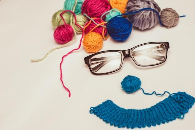 色とりどりのクルーと白い背景の上の眼鏡の変な顔。
