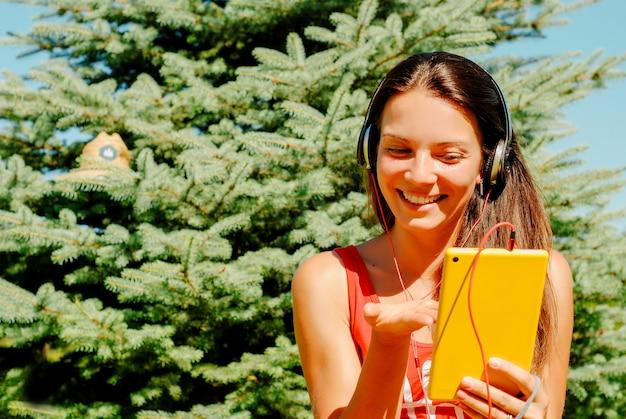 Красивая женщина с помощью планшета на открытом воздухе.