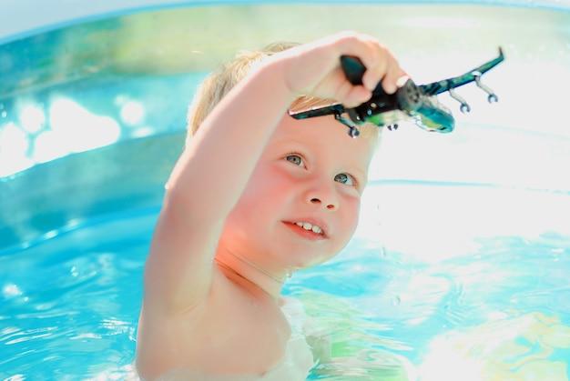 スイミングプールでおもちゃの飛行機を持つ赤ちゃん。屋外プールで泳ぐことを学ぶの少年。