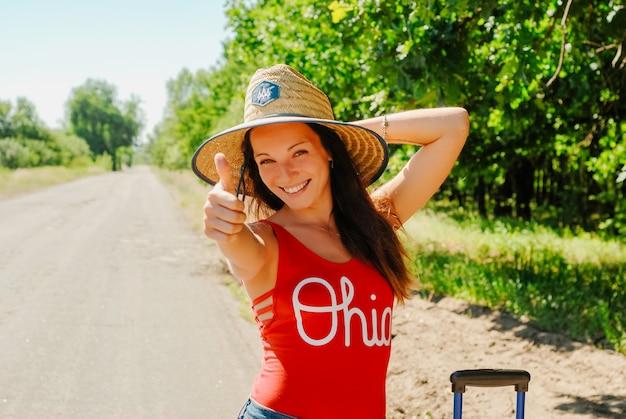 Пешие прогулки женщина в соломенной шляпе и красной рубашке, давая пальцы улыбается.
