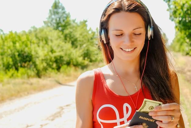 お金でパスポートを持って道にヘッドフォンを持つ美しい女性。