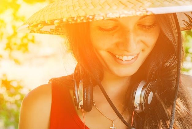ヘッドフォンで麦わら帽子の美しいブルネットの女性の肖像画。閉じる