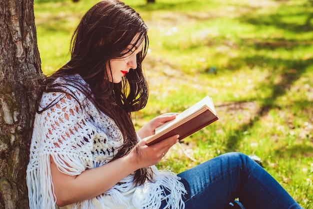 Брюнетка женщина расслабляющий чтение книги в парке