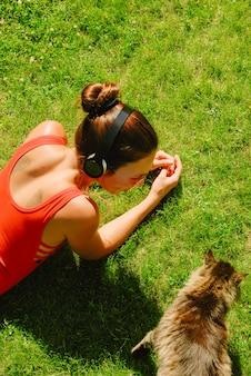 音楽、ヘッドフォンを身に着けている猫を見て赤いシャツを着た若いブルネットの女性のトップビューをお楽しみください