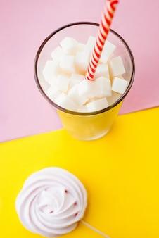 Кубики белого сахара в стакане с трубочкой