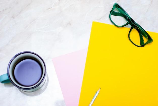 黄色のチューリップ、コーヒー、グリーングラス、大理石の背景にカラフルな紙