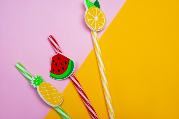 スイカ、レモン、パイナップルの形をしたピンクと黄色の背景にわら