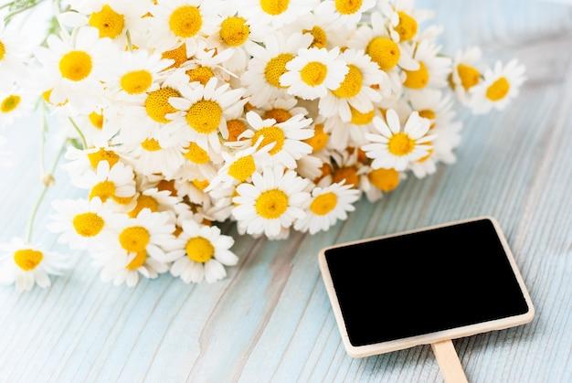 木製の背景に新鮮なカモミールの花の花束