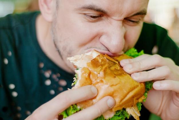 ハンバーガーを食べるレストランの男