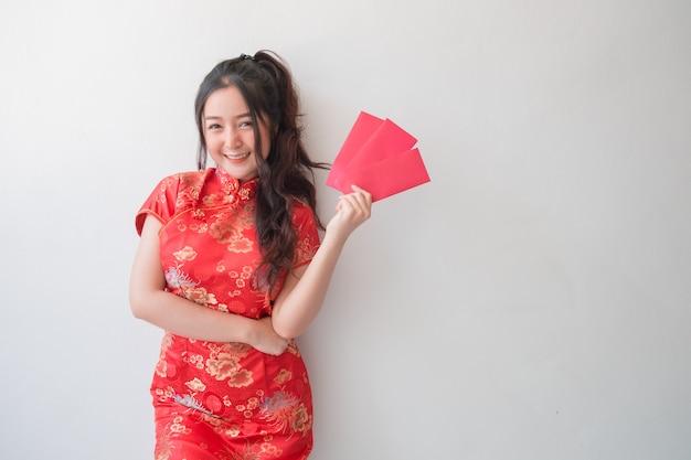 伝統的な中国のチャイナドレスを着たアジアの女性が中国の新年の赤い封筒を見せて