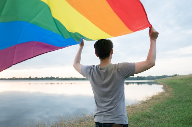 若い白人男性は虹色の旗を握って後ろから見ています。