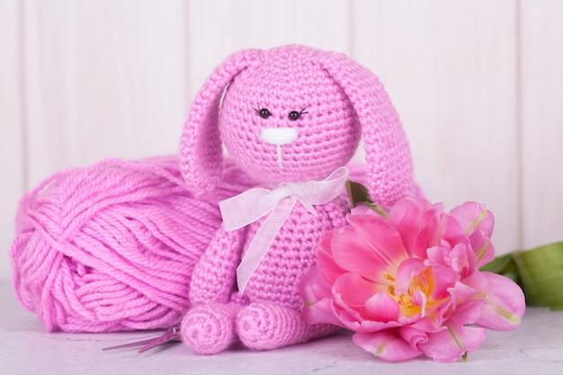 チューリップとピンクのウサギ。聖バレンタインデーの装飾。ニットおもちゃ、あみぐるみ、