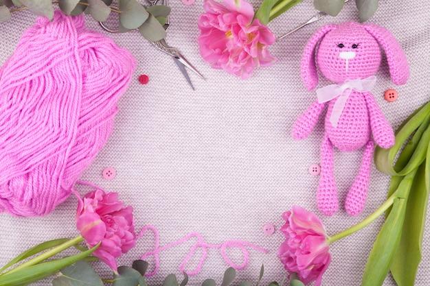 チューリップとピンクのウサギ。聖バレンタインデーの装飾。ニット玩具、あみぐるみ、創造性
