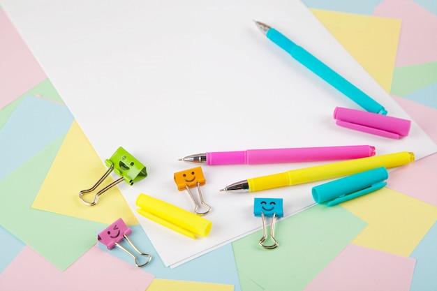 カラフルなペン、付箋、メモ帳、ペン、バインダークリップのセットです。上面図