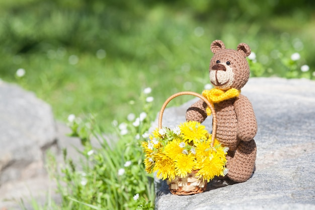Маленький вязаный бурый медведь с желтым шарфом в летнем саду. вязаная игрушка, ручная работа, амигуруми
