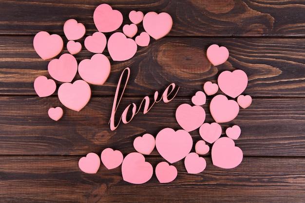 暗い背景に木のピンクの心。閉じる。バレンタイン・デー