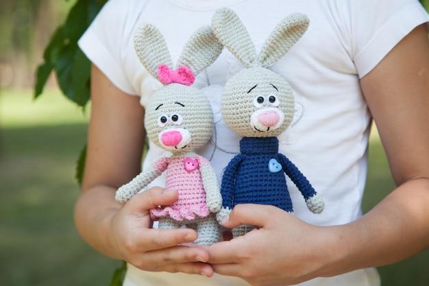 ニットのおもちゃを保持している公園の小さな女の子。手作り、あみぐるみ
