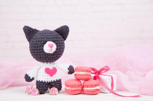 心を持つニット猫。聖バレンタインデーの装飾。ニット玩具、あみぐるみ。バレンタインの日グリーティングカード。