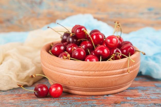 古い木製の背景に木製のボウルに甘いチェリーの多くの果実