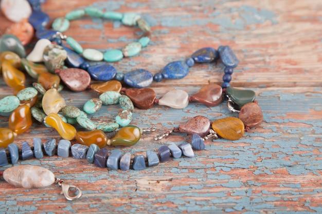 Разноцветные бусы и ожерелья из полудрагоценных камней на фоне старых деревянных. женские украшения