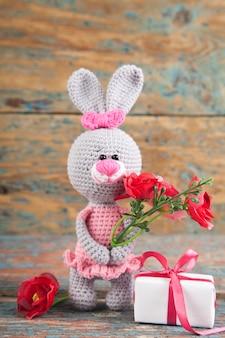 古い木製の背景にピンクのドレスの小さなニットグレーウサギ。ニットおもちゃ、手作り、裁縫。