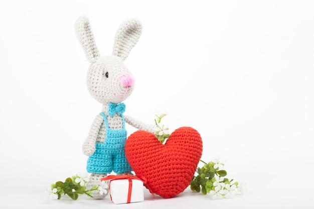 心を持つニットウサギ。聖バレンタインデーの装飾。ニットおもちゃ、あみぐるみ、グリーティングカード。