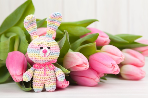 繊細なピンクのチューリップとかぎ針編みのウサギ。ニットグッズ、手作り、針仕事、あみぐるみ。