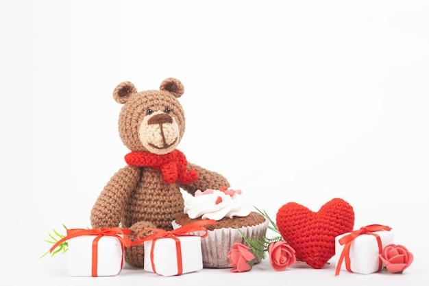 心を持つニットベア。聖バレンタインデーの装飾。ニットおもちゃ、あみぐるみ、グリーティングカード。
