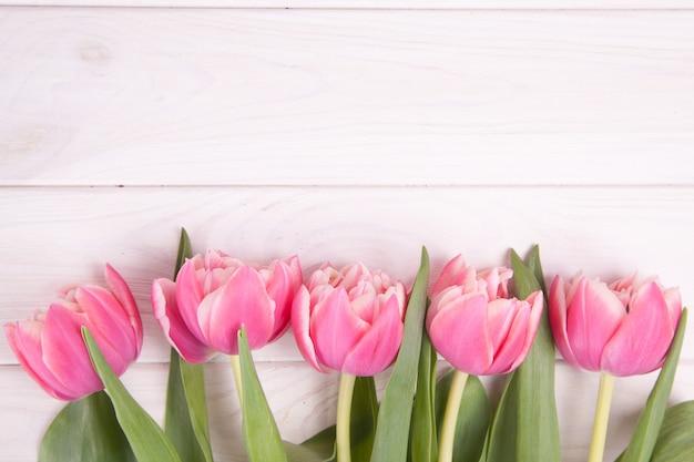 Нежные розовые тюльпаны на белом фоне деревянные. крупный план. композиция цветов. цветочный весенний фон. день святого валентина, пасха, день матери.